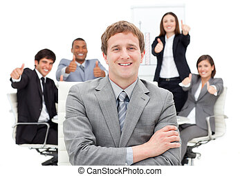 Cheerful business team punching the air in a meeting