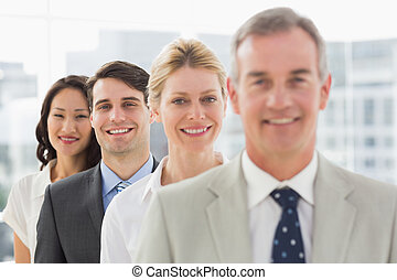 Cheerful business team standing in a line smiling at camera
