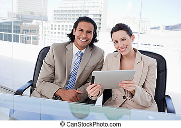 Cheerful business team using a tablet computer