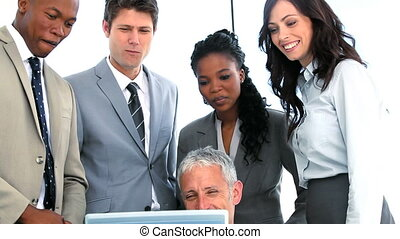 Cheerful business team working on a laptop