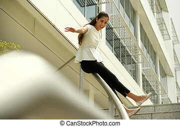 Cheerful Business Woman Going Downstairs Sliding On Rail For...