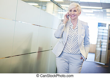 Cheerful business woman having phone call