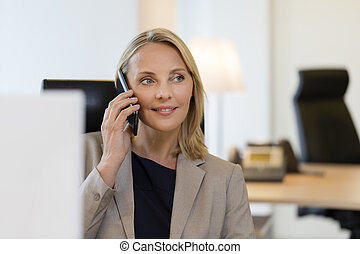 Cheerful business woman on mobile phone at office