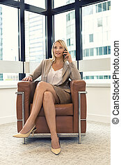 Cheerful business woman sitting in a chair. on mobile phone in modern office