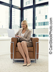 Cheerful business woman sitting in a chair. Working on laptop in modern office