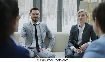 Cheerful businessman and businesswoman talking and duscussing future contract with business partners sitting on couch in meeting room