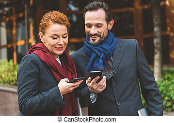 Cheerful businessman and businesswoman using smartphones