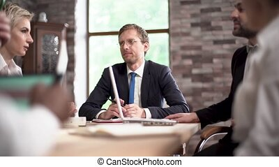 Cheerful businessman disscusses issues with his colleague in conference room