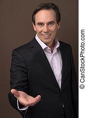 Cheerful businessman gesturing. Cheerful mature businessman gesturing and looking at camera while standing on brown background