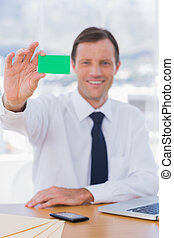 Cheerful businessman holding a green business card