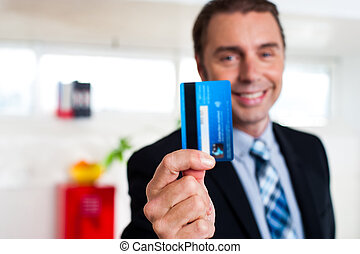 Cheerful businessman holding up his credit card