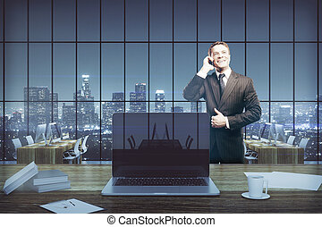 Cheerful businessman on phone in office