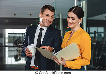 Cheerful businessman pointing on open paper folder