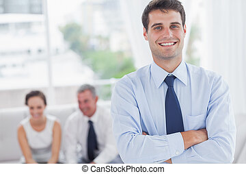 Cheerful businessman posing while his colleagues are working