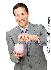 Cheerful businessman saving money in a piggy-bank