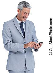 Cheerful businessman sending text message