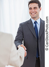 Cheerful businessman shaking hands with his new workmate