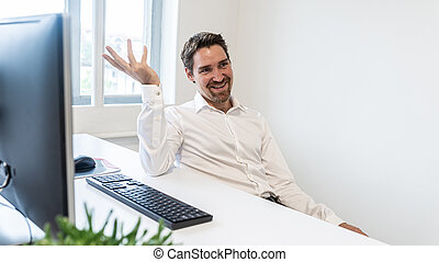 Cheerful businessman sitting at his office desk