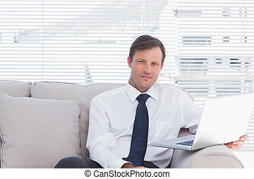 Cheerful businessman sitting on couch