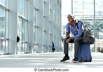cheerful businessman sitting with luggage and cellphone at station