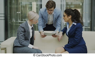 Cheerful businessman talking and discussing about financial report with business female colleagues sitting on sofa in meeting room