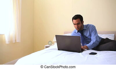 Cheerful businessman typing on notebook