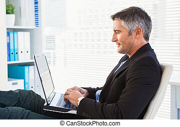 Cheerful businessman using laptop