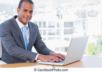 Cheerful businessman working on his laptop