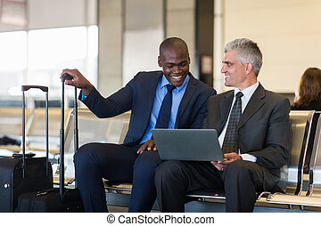 businessmen using laptop computer at airport