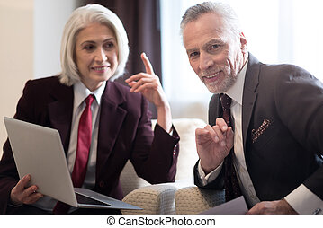 Cheerful businesswoman and her colleague working with the laptop