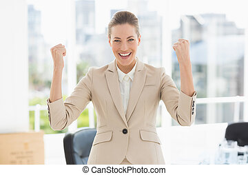 Cheerful businesswoman clenching fists in office