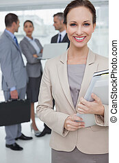Cheerful businesswoman holding files posing