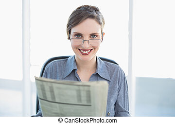 Cheerful businesswoman holding newspaper sitting at her desk
