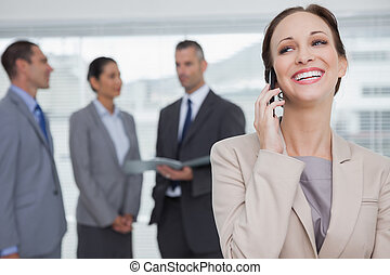 Cheerful businesswoman in bright office calling while colleagues talking together