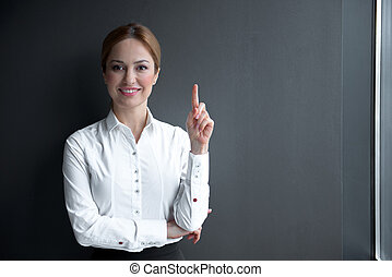 Cheerful businesswoman pointing finger up - Portrait of...