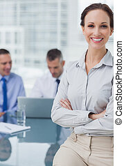 Cheerful businesswoman posing leaning against the desk