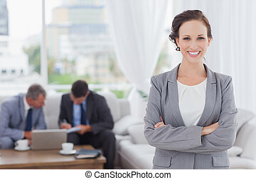 Cheerful businesswoman posing while her colleagues are working