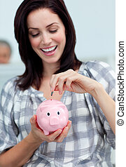 Cheerful businesswoman saving money in a piggy-bank