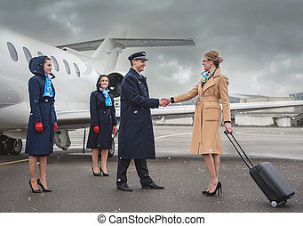 Cheerful businesswoman shaking hands aviator near plane