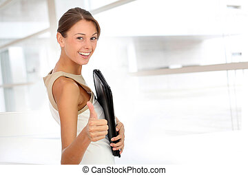 Cheerful businesswoman showing thumb up