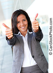 Cheerful businesswoman showing tumbs up