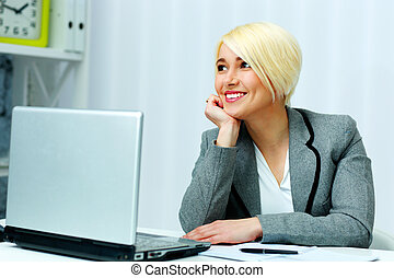 Cheerful businesswoman sitting at the table with laptop in office