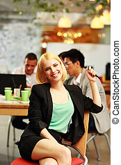 Cheerful businesswoman sitting in office, with her colleagues in background
