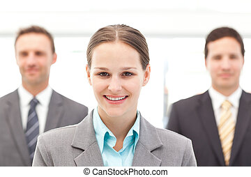 Cheerful businesswoman standing in front of two businessmen