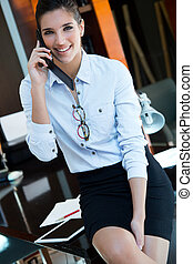 Cheerful businesswoman talking on phone standing in her office