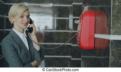 Cheerful businesswoman talking with staff with wired red...