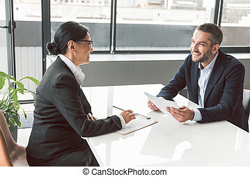 Cheerful businesswoman telling with male