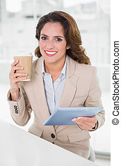 Cheerful businesswoman using digital tablet at her desk holding disposable cup in bright office