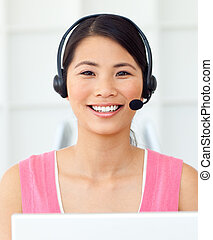 Cheerful businesswoman using headset in a call center
