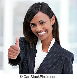 Cheerful businesswoman with a thumb up standing in the...